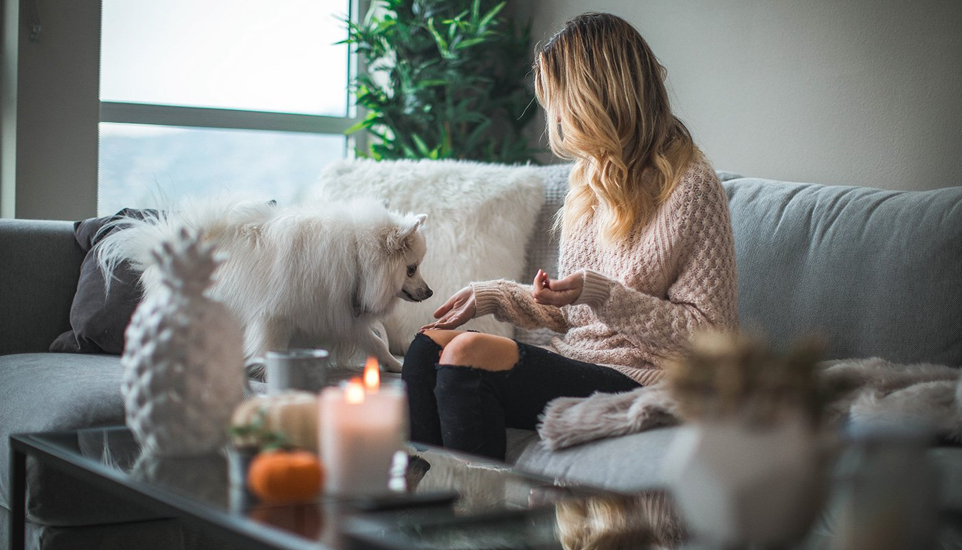 Girl at home with dog and scented candle