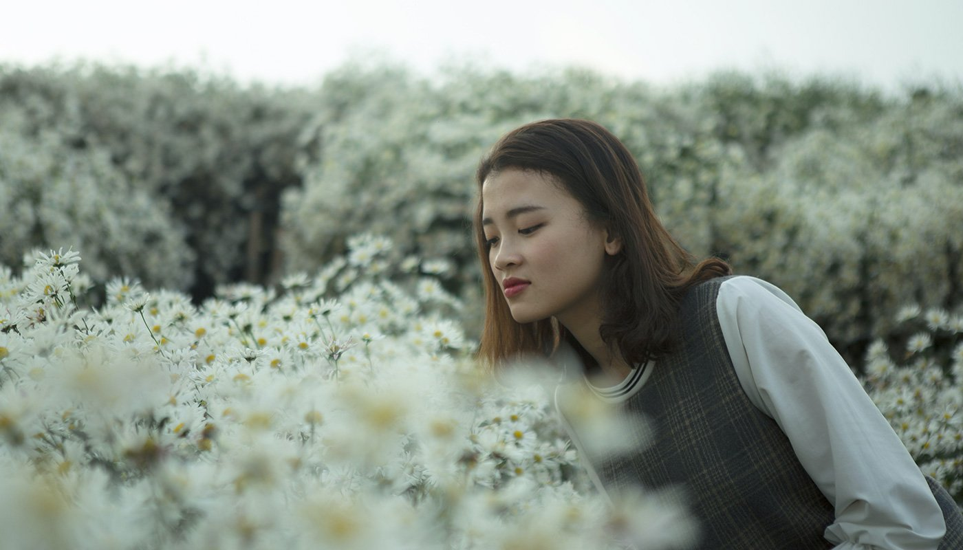 Girl is smelling white flowers