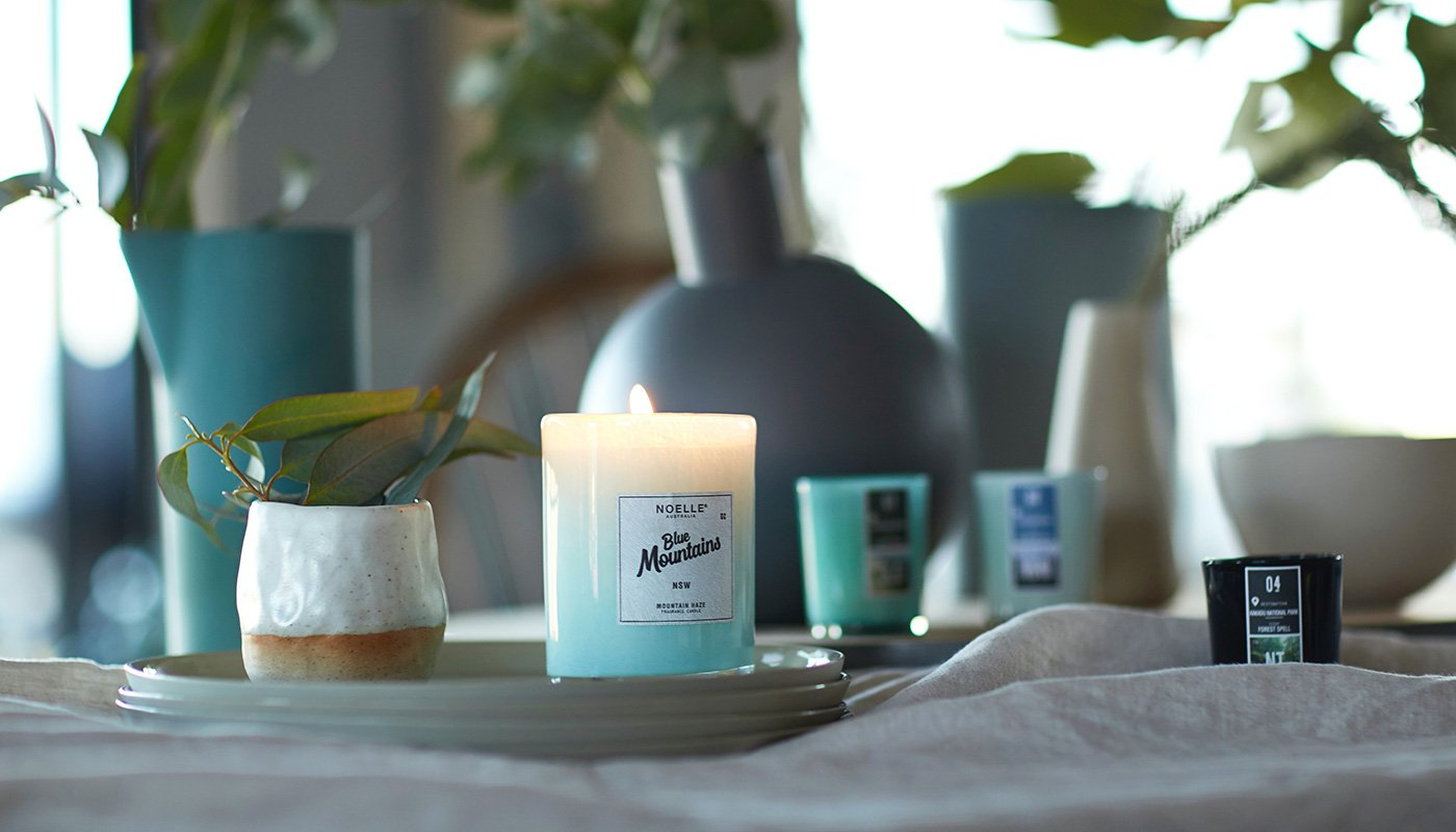 Scented candle on the table with fresh flowers
